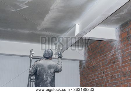 A Worker Paints A Ceiling From A Spray Gun. Painting Work At A Construction Site.