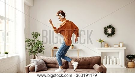 Positive Young Lady In Wireless Headphones And Casual Clothes Listening To Music With Pleasure And D