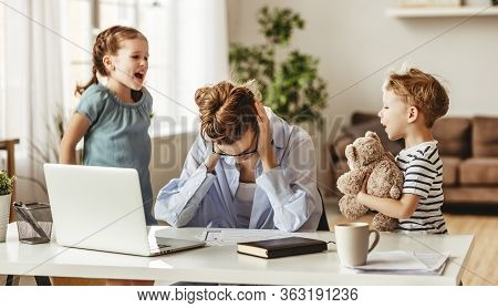 Small Mischievous Kids Noising And Distracting Mother Freelancer Trying To Concentrate On Laptop And