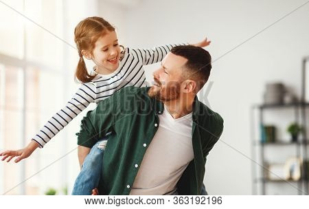 Happy Young Man Giving Piggyback Ride To Cheerful Little Daughter While Enjoying Time Together At Ho