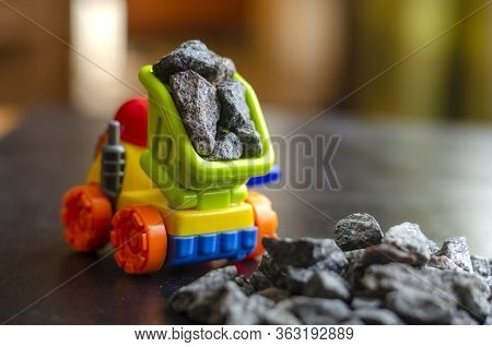 Colorful Plastic Toy For Children Dump Truck. Multi-colored Dump Truck With Rubble In The Back. A Pi