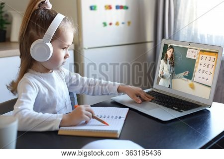 Smart Small Preschooler Girl In Headphones Watch Online Lesson And Communicate With Teacher At Home,