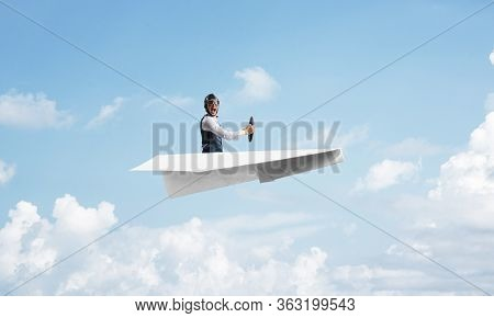 Businessman In Aviator Hat Sitting In Paper Plane And Holding Steering Wheel. Pilot Driving Paper Pl