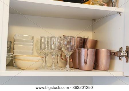 Mugs, Glass And Ramekins In A Kitchen Cupboard