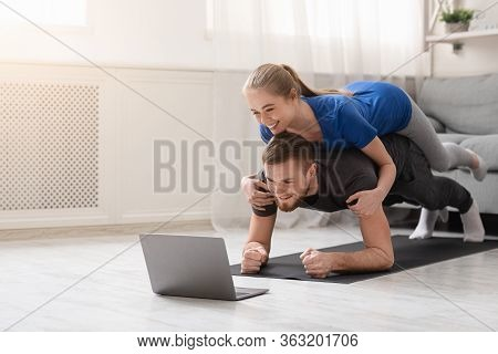 Online Workout. Young Man And Woman Practicing Plank Exercise With Online Tutorial At Home, Free Spa