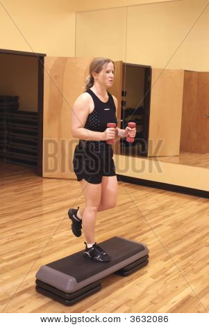 Blonde Woman Working Out In The Gym With Hand Weights