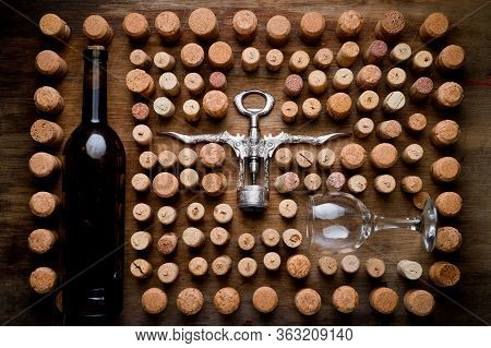 Wine Corks Of Different Sizes, A Corkscrew, A Bottle Of Wine And A Glass Shot On An Old Wooden Surfa