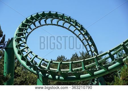 Loop And Turn On A Green Roller Coaster In An Amusement Park