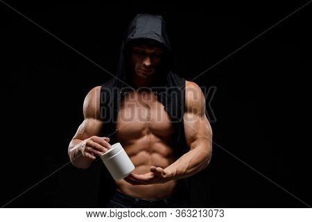 Muscular Bodybuilder With Jar Of Protein On A Black Background. Sports Nutrition. Bodybuilding Nutri