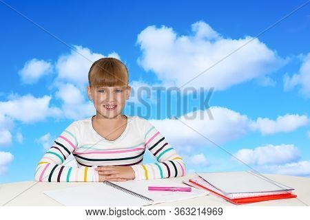 Education, People, Children And School Concept - Little Student Girl Sitting At Table With Notebooks