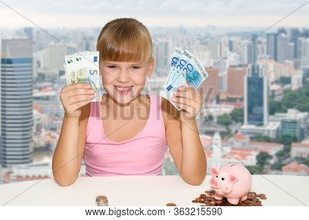Little Cheerful Girl Sitting On The Desk With Coins And Pink Piggy Bank And Holding In Hands Europea