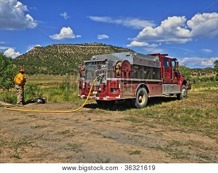 Firefighter pumping water into tanker