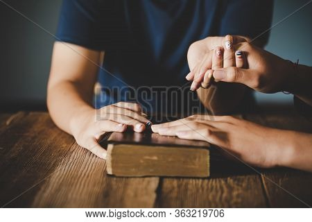 Couple Teen Boy And Girl Are Holding Hands And Pray Together On Wooden Table With The Light From Sid