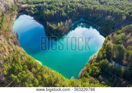 Concept Of Loving To Nature . Lake In Heart Shape In Green Forest From Above. Green Summer Landscape