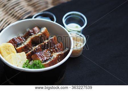 Side View Of Unadon Or Unagi Donburi Or Eel Bowl Is A Dish Originating In Japan On Black Background.