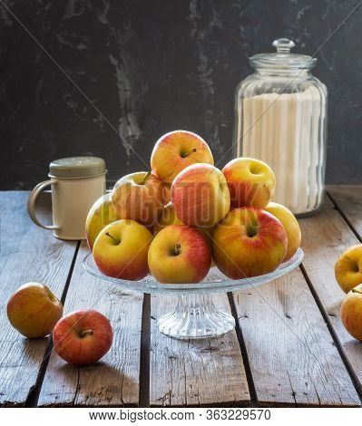Set For Making Apple Pie. Fresh Apples In A Glass Vase, Flour In A Glass Jar And Icing Sugar In A Hi