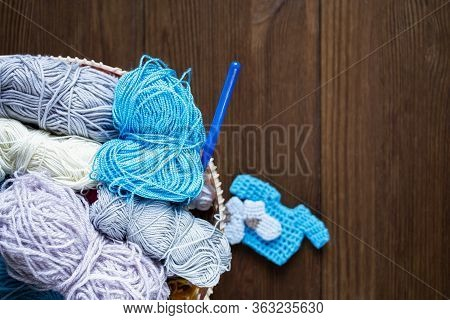 On A Wooden Table Is A Basket With Knitting Yarn And Crochet. Fons Knitting And With Copy Space.