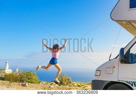 Woman Enjoying Trip With Rv Motor Home, Jumping In The Air At Camper. Mesa Roldan Lighthouse Locatio