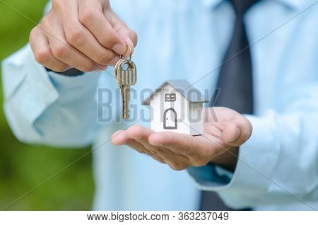 Businessman With House Model And Keys, Real Estate Agent With House Model And Keys