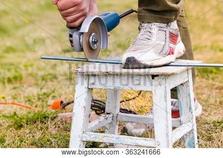 Man Cutting Metal Tack By Electric Angle Grinder, Working Process