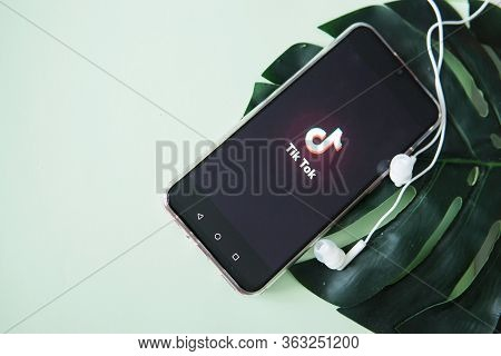 Tver, Russia-april 9, 2020, The Tik Tok Logo On The Smartphone Screen On Mint Background With Headph