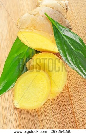 Sliced ginger Root And Green Leaves On A Wooden Board. The Concept Of A Healthy Food, A Cure For T