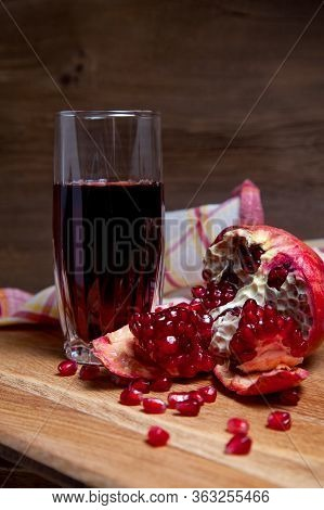 Fresh Red Pomegranate And Glass Of Fresh Rudy Juice On A Wooden Background..