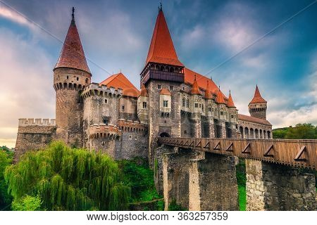 Popular Tourist Location, Majestic Old Medieval Corvin Castle With High Towers, Bastions And Wooden