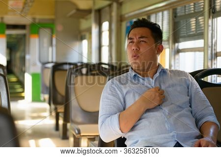 Stressed Overweight Asian Tourist Man Feeling Hot Inside The Train
