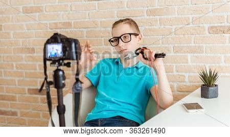 Young Teen Boy Blogger Setting Up Camera For Recording Live Vlog Video Tutorial Session At Home. It