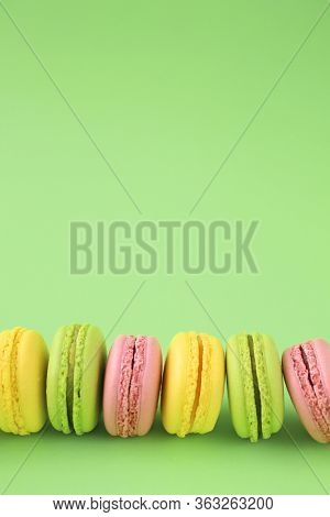 Row of traditional french macarons on green background