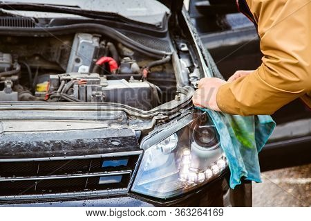 A Man Changes His Headlights. Replacing The Headlight Lamps, The Hood Is Open. Car Service And Clean