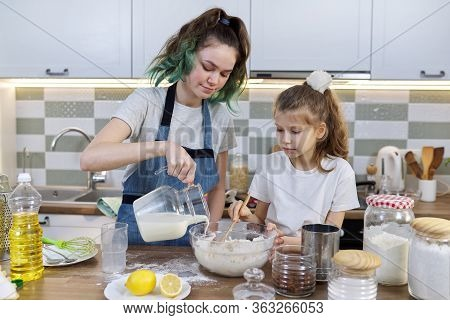 Children Two Girls Sisters Preparing Muffins In Home Kitchen, Add Milk To Dough. Old Teenage Girl Wi