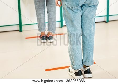 People Stand In Line, Legs Close-up. Attention Line On The Floor Of The Store To Maintain Social Dis