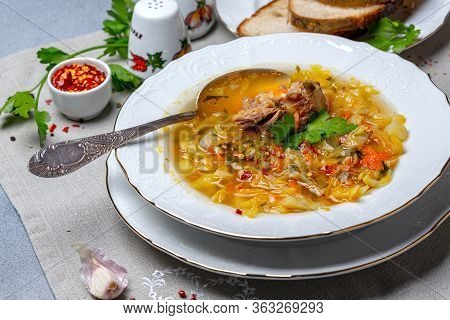 Soup Of Oxtails, Cabbage, Vegetables And Fresh Parsley In A White Porcelain Plate On A Linen Napkin,