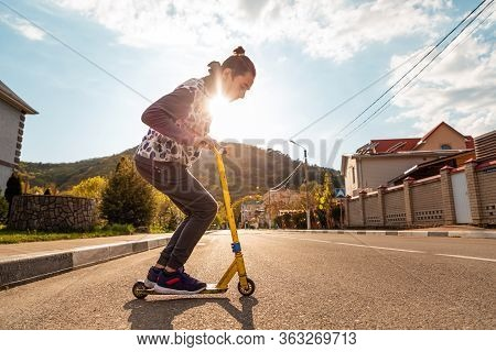 A Teenager Squats On A Scooter, Preparing To Perform A Trick. In The Background Is An Empty Street A