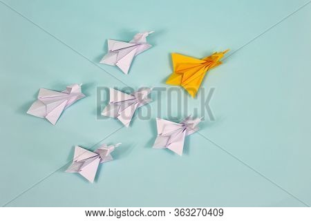 Origami. Paper Swans On A Blue Background. Leadership Concept. An Orange Swan Leads A Flock Of White