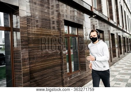 Healthy Habits During Quarantine. Young Man In Sports Clothing In Medical Mask On The Face Is Runnin