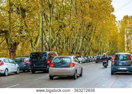 Streets Of Rome, Italy. Beautiful Lush Tall Trees And Parked Cars Along Sidewalk Of City Street. Sma