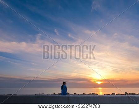 Silhouette Of A Woman In The Blue Shirt On The Pink Sunset Background