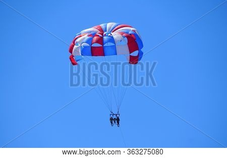 A Distance View Of Parasailing Excursion On A Bright Sunny Day Near Near Madeira Beach, Florida, U.s
