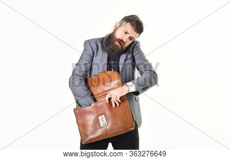 Mid Adult Businessman Balancing Briefcase And Using Mobile Phone.