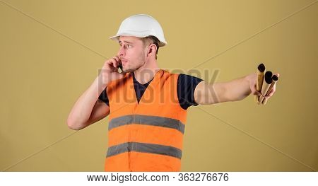 Man Supervises Construction On Phone, Ocher Background. Supply Of Building Materials Concept. Engine