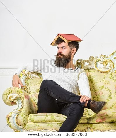 Macho Sits With Open Book On Head, Like Roof. Man With Beard And Mustache Sits On Sofa, White Wall B