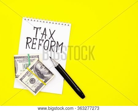 A White Notepad With The Words Tax Reform, Money And A Black Marker On A Yellow Background. The Conc