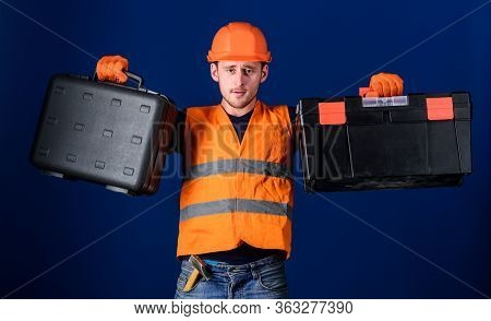 Toolbox And Equipment Concept. Man In Helmet, Hard Hat Holds Toolbox And Suitcase With Tools, Blue B