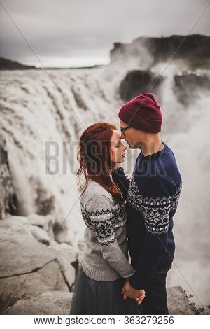 Young Stylish Couple In Love Kissing Together Near Famous Icelandic Landscape Dettifoss Waterfall. T