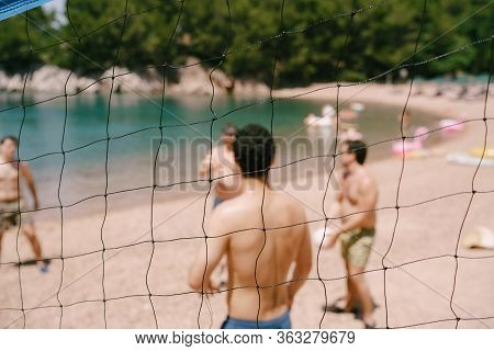 Volleyball Net On The Beach. Close-up Of The Volleyball Net. People On The Beach Play Volleyball