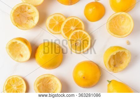 High angle shot of lemon rinds, whole lemons and lemon slices on a white marble kitchen surface.
