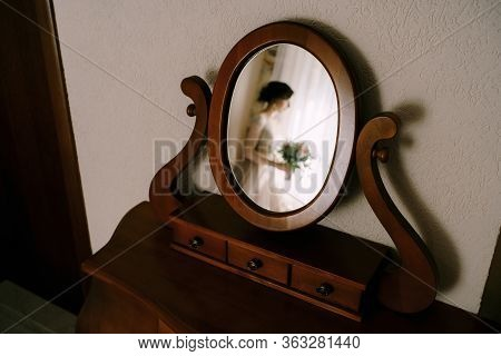 Reflection Of The Bride With A Bouquet In Her Hands In An Old Mirror On The Table For Make-up